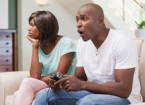 bored_woman_sitting_next_to_her_boyfriend_playing_video_cg6p9559930c_th